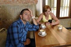 Les jeunes couples au téléphone portable de café s'adonnent à la femme ignorant l'homme frustrant Images libres de droits