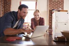Les jeunes couples blancs utilisant l'ordinateur portable dans la cuisine, se ferment  Photos libres de droits