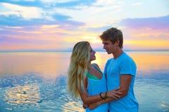 Les jeunes couples blonds étreignent dans le lac de mer de coucher du soleil heureux photographie stock libre de droits