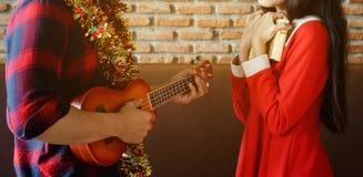 Les jeunes couples célèbrent Noël avec l'ukulélé Images libres de droits