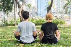 Les jeunes couples d'amour faisant une méditation pour calmer leur esprit après l'exercice en parc encerclent avec un soleil lége Images libres de droits