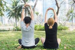 Les jeunes couples d'amour faisant une méditation pour calmer leur esprit après l'exercice en parc encerclent avec un soleil lége images stock