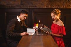 Les jeunes couples d'amour regardent le menu dans le restaurant Photographie stock libre de droits
