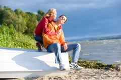 Les jeunes couples d'amour se reposent sur le bateau sur le côté du fleuve Photographie stock