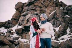 Les jeunes couples dans les chapeaux, les écharpes et des jeans humides avec des tasses de thé chaud dans leurs mains pendant l'h Image stock