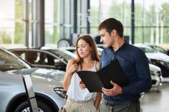 Les jeunes couples dans des vêtements élégants d'heure d'été choisissent une nouvelle voiture au concessionnaire automobile photographie stock