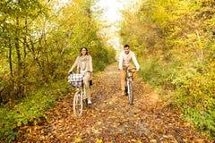 Les jeunes couples dans des vêtements chauds faisant un cycle en automne se garent Image libre de droits