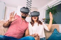 Les jeunes couples dans des vêtements sport portent les lunettes de réalité virtuelle Photo stock