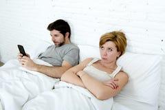 les jeunes couples dans l'épouse mécontente de lit ont ennuyé frustrant et fâché tandis que le mari d'intoxiqué d'Internet emploi Photo stock