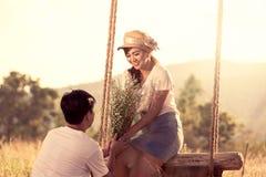 Les jeunes couples dans l'amour dans le pré mettent en place le jour ensoleillé Image stock