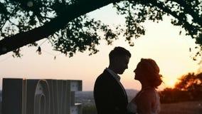 Les jeunes couples dans l'amour dans des robes de soirée sont les lettres proches debout de lumière d'amour Photographie stock