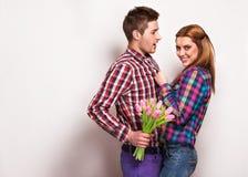 Les jeunes couples dans l'amour font un coeur et les mains tiennent des tulipes. Image stock
