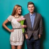 Les jeunes couples dans l'amour font un coeur et les mains tiennent des tulipes. Images stock