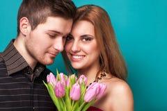 Les jeunes couples dans l'amour font un coeur et les mains tiennent des tulipes. Image libre de droits