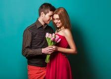 Les jeunes couples dans l'amour font un coeur et les mains tiennent des tulipes. Photographie stock libre de droits