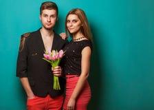 Les jeunes couples dans l'amour font un coeur et les mains tiennent des tulipes. Photo stock