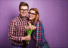 Les jeunes couples dans l'amour font un coeur et les mains tiennent des tulipes. Photos libres de droits