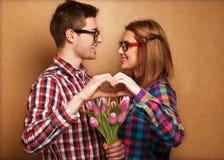 Les jeunes couples dans l'amour font un coeur et les mains tiennent un bouque Photos libres de droits