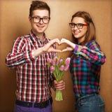 Les jeunes couples dans l'amour font un coeur et les mains tiennent un bouque Photos stock