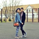 Les jeunes couples dans l'amour marchant dans la ville garent tenir des mains Photos stock