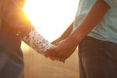 Les jeunes couples dans l'amour marchant pendant l'automne garent tenir le lo de mains Images libres de droits