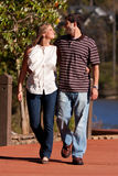 Les jeunes couples dans l'amour marchent par un lac Image stock