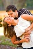Les jeunes couples dans l'amour partagent une étreinte d'amusement Image stock