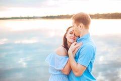 Les jeunes couples dans l'amour s'étreignent au lac extérieur dans le jour d'été, concept d'harmonie Image stock
