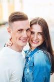 Les jeunes couples dans l'amour s'étreignent dans la ville Photos stock