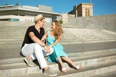 Les jeunes couples dans l'amour se reposent sur les étapes et parler Photographie stock libre de droits