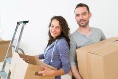 Les jeunes couples dans l'amour se sont déplacés leur nouvel appartement Image stock