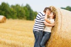 Les jeunes couples dans l'amour sur le foin jaune mettent en place la soirée d'été. Photos stock