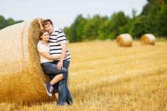 Les jeunes couples dans l'amour sur le foin jaune mettent en place la soirée d'été. Photo stock