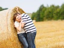 Les jeunes couples dans l'amour sur le foin jaune mettent en place la soirée d'été. Image stock
