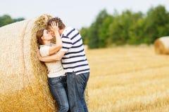 Les jeunes couples dans l'amour sur le foin jaune mettent en place la soirée d'été Photo stock