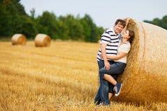 Les jeunes couples dans l'amour sur le foin jaune mettent en place la soirée d'été Photographie stock