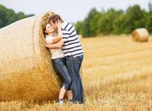 Les jeunes couples dans l'amour sur le foin jaune mettent en place la soirée d'été Photo libre de droits