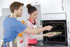 Les jeunes couples dans la cuisson d'amour durcissent en four Photographie stock