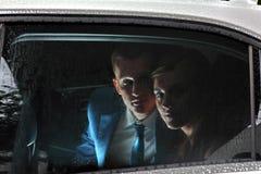 Les jeunes couples dans la voiture de salon, nouveaux mariés regardent la fenêtre Images libres de droits