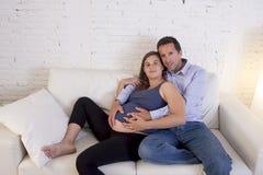 Les jeunes couples dans le divan de salon d'amour à la maison avec la femme soient Photo stock