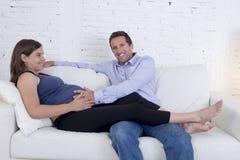 Les jeunes couples dans le divan de salon d'amour à la maison avec la femme soient Photographie stock libre de droits
