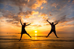 Les jeunes couples dans un saut sur la mer échouent Image libre de droits