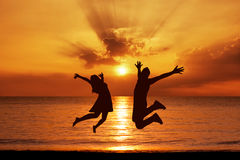 Les jeunes couples dans un saut sur la mer échouent au coucher du soleil Photos stock