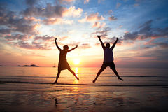 Les jeunes couples dans un saut sur la mer échouent au coucher du soleil Photos libres de droits