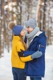 Les jeunes couples dans les vêtements lumineux se tiennent et semblent face à face dans une forêt Photo stock