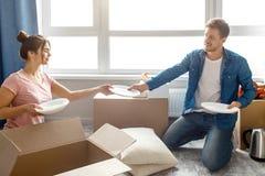 Les jeunes couples de famille ont acheté ou ont loué leur premier petit appartement Femme d'aide d'homme avec le déballage Déména photo libre de droits