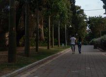 Les jeunes couples de l'adolescence adultes marchant à partir de la caméra sur l'allée pavée par parc vert au coucher du soleil a photo stock