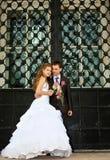 Les jeunes couples de mariage restent près de la porte énorme Images libres de droits