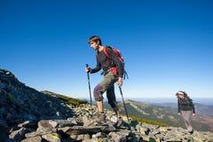 Les jeunes couples de randonneur marchant vers le haut de rocheux la montagne complètent Photos stock