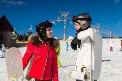 Les jeunes couples de sourire dans des costumes de ski, des casques et des lunettes de ski se tiennent Images stock